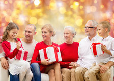 Happy family with christmas gifts over lights Royalty Free Stock Images