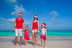 Happy family in Christmas Hats on white beach Royalty Free Stock Photography