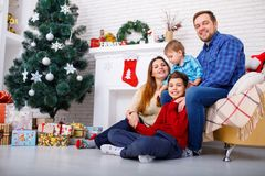 Happy family at Christmas in the house on background of Christmas trees and a fireplace, concept of holidays, new year. Stock Photo