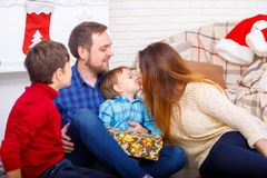 Happy family at Christmas in the house, mom kisses son concept of holidays, new year. Stock Photo