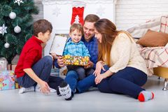 Happy family at Christmas in the house near the Christmas tree, with gifts. Stock Image