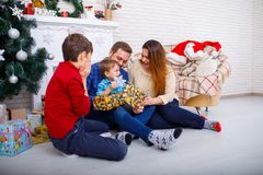 Happy family at Christmas in the house unpacking presents. Stock Photography