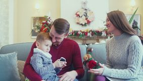 Happy family in a Christmas interior. Mom playing with baby. Beautiful parents and son in a New Year`s interior. Parents and son in a cozy knit sweater sitting stock video footage