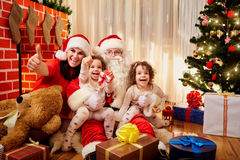 Happy family at Christmas. Mom with kids and Santa Claus in the Stock Photos