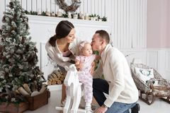 Happy young family in Christmas morning in home. dad kisses daughter. Happy new year Royalty Free Stock Photos