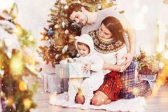 Happy family at christmas in morning opening gifts together near the fir tree. The concept of family happiness and well stock photos