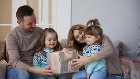 Happy family at Christmas, mum, dad and two little girls sitting at home on the sofa near the Christmas tree to open the. Gifts stock video