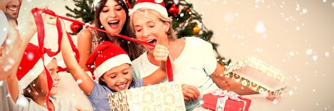 Composite image of happy family at christmas opening gifts together. Happy family at christmas opening gifts together against snow falling royalty free stock photography