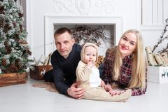 Happy family at Christmas. The parents and the baby lying on the floor and smiling. In the background stands and Christmas tree ornaments Stock Images