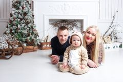 Happy family at Christmas. The parents and the baby lying on the floor and smiling. In the background stands and Christmas tree ornaments Stock Photos