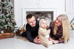 Happy family at Christmas. The parents and the baby lying on the floor and smiling. In the background stands and Christmas tree ornaments Royalty Free Stock Photos