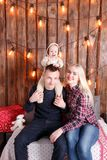 Happy family at Christmas. The parents and the baby sitting. Wall of wooden planks and garland.  Royalty Free Stock Images