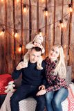 Happy family at Christmas. The parents and the baby sitting. Wall of wooden planks and garland.  Royalty Free Stock Photos