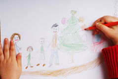 Happy family at Christmas time. Little girl drawing happy family at christmas time royalty free stock images