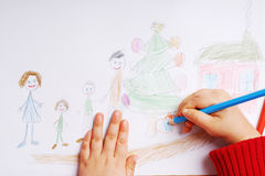 Happy family at Christmas time. Little girl drawing family at christmas Stock Photo