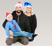 Happy family by the Christmas Tree. Happy family of 3 people in caps of Santa Claus, the Christmas tree and the fireplace in the Christmas night.On a gray stock images