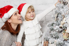 Happy family and Christmas tree. The pretty girl with mum are decorating a Christmas tree in the house. Happy family Royalty Free Stock Image