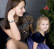 Happy family at christmas tree sitting home smiling, waiting for father at holiday evening Stock Photos