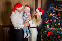 Happy family and Christmas tree. Young family with  little son stand near Christmas tree in the room. Merry Christmas and Happy New Year Royalty Free Stock Photography