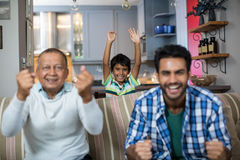 Happy family clenching fist while watching soccer match Royalty Free Stock Photo
