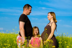 Happy Family  with Clouds and Grass. Happy pregnant  Family  with Clouds and Grass Stock Photo