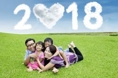 Happy family with clouds shaped number 2018 Royalty Free Stock Photos