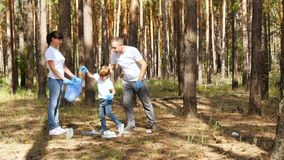 Happy family collects garbage in the forest. Dad and son put the garbage in a bag. The mother and father raise the child