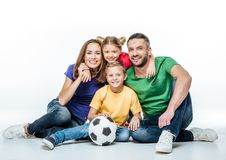 Happy family in colored t-shirts sitting together with soccer ball stock photos