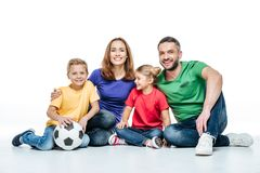Happy family in colored t-shirts sitting together with soccer ball royalty free stock image
