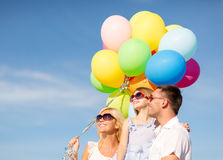 Happy family with colorful balloons outdoors Stock Photos