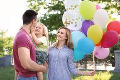 Happy family with balloons outdoors on sunny day. Happy family with colorful balloons outdoors on sunny day Royalty Free Stock Image