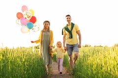 Happy family with balloons outdoors on sunny day. Happy family with colorful balloons outdoors on sunny day Stock Photo