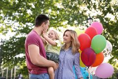 Happy family with balloons outdoors on sunny day. Happy family with colorful balloons outdoors on sunny day Royalty Free Stock Images