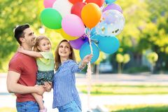 Happy family with balloons in park on sunny day. Happy family with colorful balloons in park on sunny day Royalty Free Stock Images