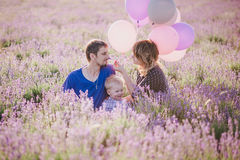 Happy family with colorful balloons posing in a lavender field Stock Photography