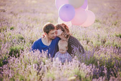 Happy family with colorful balloons posing in a lavender field Stock Image