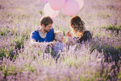 Happy family with colorful balloons posing in a lavender field Stock Photos