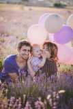 Happy family with colorful balloons posing in a lavender field Royalty Free Stock Image