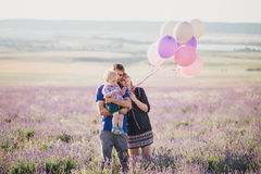 Happy family with colorful balloons posing in a lavender field Royalty Free Stock Photos