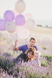 Happy family with colorful balloons posing in a lavender field Royalty Free Stock Images