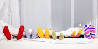 Happy family in colorful socks on white bed. Stock Photos