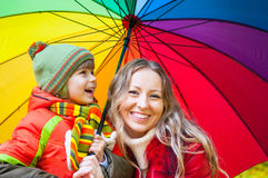 Happy family with colorful umbrella in autumn park. Happy family with bright multicolored umbrella in autumn park stock photography