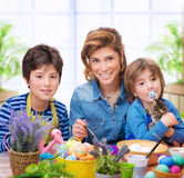 Happy family coloring eggs Stock Image