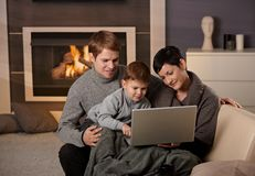 Happy family with computer. Happy family sitting on couch at home in winter, using laptop computer, smiling royalty free stock photography