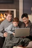 Happy family with computer. Woman sitting on sofa at home on a cold winter day, drinking hot tea, looking down Stock Photos