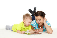 Happy family with computer tablet. Young mother and her little son with computer tablet lie on a white background. Happy family stock images