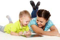 Happy family with computer tablet. Young mother and her little son with computer tablet lie on a white background. Happy family royalty free stock image