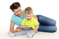 Happy family with computer tablet. Young mother and her little son with computer tablet sit on a white background. Happy family royalty free stock photo