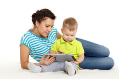 Happy family with computer tablet. Young mother and her little son with computer tablet sit on a white background. Happy family royalty free stock image