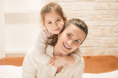 Happy family concept. Beautiful little girl embracing her mother while sitting on the bed at home. Mothers day. Mother and little lovely daughter Royalty Free Stock Photo